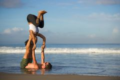 Молодые привлекательные и сконцентрированные пары акробатов практикуя баланс йоги acro и тренировку раздумья на красивом пляже вн стоковые изображения rf