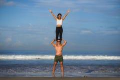 Молодые привлекательные и сконцентрированные пары акробатов практикуя баланс йоги acro и тренировку раздумья на красивом пляже вн стоковое фото rf