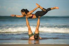 Молодые привлекательные и сконцентрированные пары акробатов практикуя баланс йоги acro и тренировку раздумья на красивом пляже вн стоковые фотографии rf