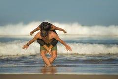Молодые привлекательные и сконцентрированные пары акробатов практикуя баланс йоги acro и тренировку раздумья на красивом пляже вн стоковые изображения