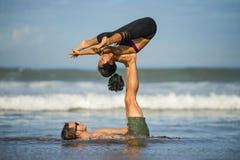 Молодые привлекательные и сконцентрированные пары акробатов практикуя баланс йоги acro и тренировку раздумья на красивом пляже вн стоковое изображение rf