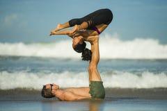 Молодые привлекательные и сконцентрированные пары акробатов практикуя баланс йоги acro и тренировку раздумья на красивом пляже вн стоковая фотография rf