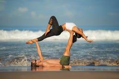 Молодые привлекательные и сконцентрированные пары акробатов практикуя баланс йоги acro и тренировку раздумья на красивом пляже вн стоковые фото