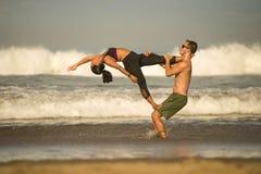 Молодые привлекательные и сконцентрированные пары акробатов практикуя баланс йоги acro и тренировку раздумья на красивом пляже вн стоковое изображение