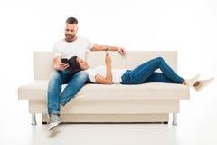 молодые привлекательные пары используя их smartphones на софе, Стоковые Фотографии RF