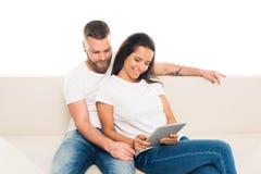молодые привлекательные пары используя цифровую таблетку, стоковая фотография rf