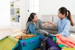 Молодые привлекательные подруги пакуя багаж Стоковая Фотография RF