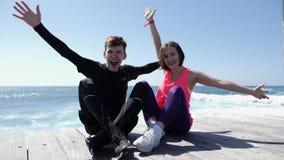 Молодые привлекательные счастливые пары поднимая руки вверх в усаживании воздуха усмехаясь и веселя на пляже сток-видео