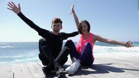 Молодые привлекательные счастливые пары поднимая руки вверх в усаживании воздуха усмехаясь и веселя на пляже ( сток-видео
