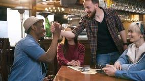 Молодые пробуренные люди используя умный телефон в баре, паб когда их мужские друзья приходя встретить их сток-видео