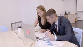 Молодые профессионалы работая на столе с компьтер-книжкой в современном офисе акции видеоматериалы