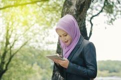 Молодые профессиональные женщины в костюме с платой над городским backgr парка Стоковое Изображение RF