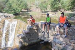 Молодые путешественники, hikers сидят около водопада Стоковое Изображение RF