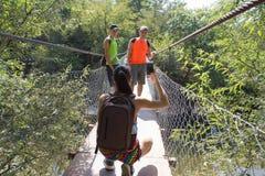 Молодые путешественники, hikers с рюкзаком принимают фото на висячем мосте Стоковые Изображения RF
