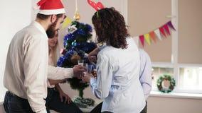 Молодые работники офиса говоря когда их коллега придет вверх по держать бутылку с игристым вином и стеклами и лить сток-видео