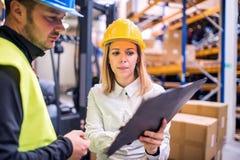 Молодые работники склада работая совместно стоковое изображение rf