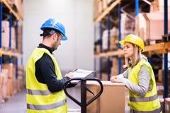 Молодые работники склада работая совместно стоковые фото