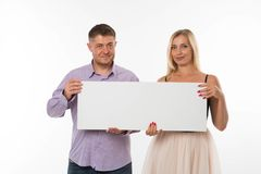 Молодые радостные пары показывая представление указывая плакат стоковая фотография