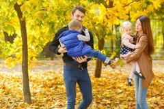 Молодые родители идут с 2 детьми в парке осени Стоковые Фото