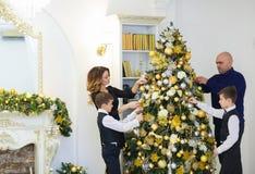 Молодые родители и дети украшая ель дома около камина стоковая фотография rf