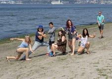 Молодые родственники поражают представление потехи на семейный отдых, пляж Alki, Сиэтл Вашингтон стоковое изображение rf