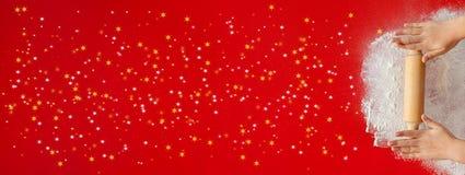 Молодые руки со звездами вращающей оси и рождества брызгают на красном цвете стоковые изображения rf