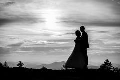 Молодые руки удерживания невесты groom и женщины взрослого мужчины на пляже на заходе солнца стоковые изображения