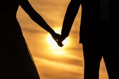 Молодые руки удерживания невесты groom и женщины взрослого мужчины на пляже на заходе солнца стоковые фотографии rf