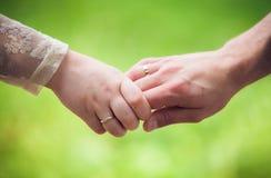 Молодые руки удерживания пар Стоковая Фотография