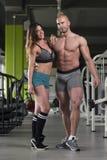 Молодые сексуальные пары фитнеса представляя в спортзале Стоковые Изображения RF
