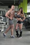 Молодые сексуальные пары фитнеса представляя в спортзале Стоковое фото RF