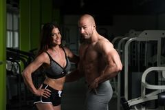 Молодые сексуальные пары фитнеса представляя в спортзале Стоковое Изображение RF