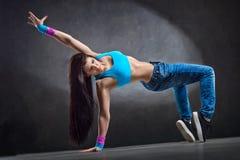 Молодые сексуальные танцы танцора женщины на предпосылке стены Стоковые Изображения