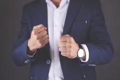 Молодые сердитые кулаки человека на темной предпосылке стоковое фото