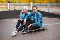 Молодые скейтбордисты парня и девушки, outdoors на яркий день осени Стоковые Изображения RF