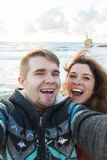 Молодые смеясь над пары принимающ selfie с умным телефоном Счастливый молодой человек и женщина принимая автопортрет с морем или Стоковые Фото