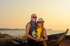 Молодые смеясь объятия пар около деревянной шлюпки на предпосылке моря Пары в любов на заходе солнца на seashore стоковое изображение