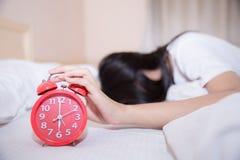 Молодые спать женщина и будильник в спальне стоковые фотографии rf