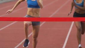 Молодые спортсмены бежать на стадионе, пересекая линии отделки в замедлении сток-видео