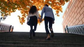 Молодые стильные пары человека и женщины идя вверх на лестницу Ноги студентов взбираются старые ретро лестницы города в падении видеоматериал