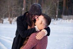 Молодые страстные пары обнимая на зимний день на парке стоковая фотография