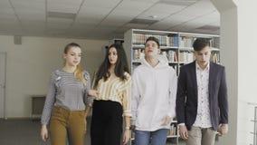 Молодые студенты идя в университетскую библиотеку сток-видео