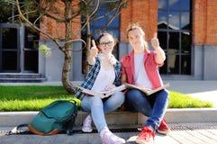 Молодые студенты показывают большие пальцы руки визирования вверх и удачу Стоковые Изображения RF