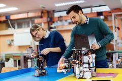 Молодые студенты робототехники подготавливая робот для испытывать Стоковое Изображение RF