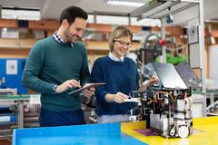 Молодые студенты робототехники подготавливая робот для испытывать Стоковое фото RF
