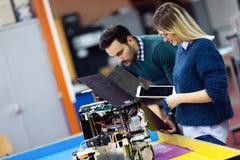 Молодые студенты робототехники подготавливая робот для испытывать Стоковое Изображение