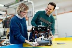 Молодые студенты робототехники подготавливая робот для испытывать Стоковое Фото