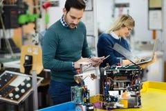 Молодые студенты робототехники подготавливая робот для испытывать Стоковые Фото