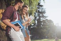 Молодые студенты читая в парке Стоковые Изображения