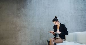 Молодые студент или коммерсантка сидя на столе в комнате в библиотеке или офисе, используя планшет стоковое фото
